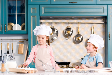 children in chef hats and aprons cooking together in kitchen