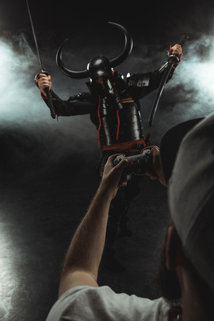 man controlling samurai character with gamepad on black
