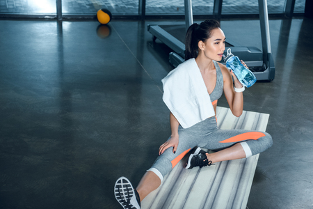 exhausted athletic woman drinking water while sitting on yoga mat at gym