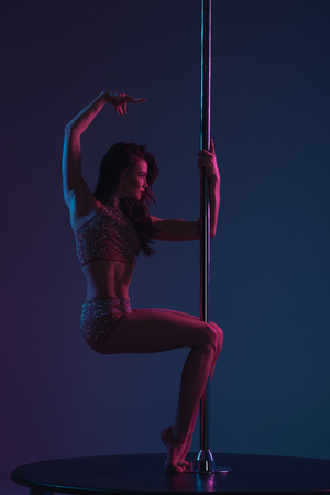 sensual sporty girl dancing with pole on blue