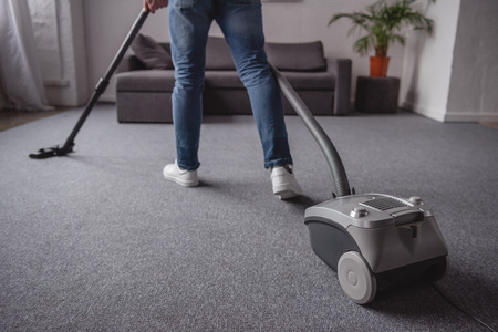cropped image of man cleaning carpet with vacuum cleaner in living room