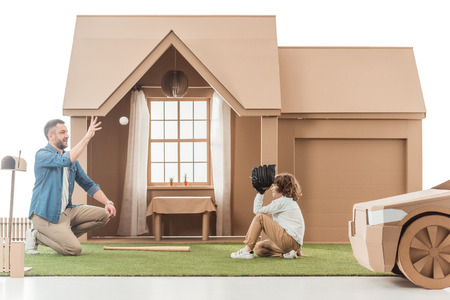 father teaching his son how to play baseball on yard of cardboard house