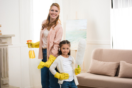 happy mother and daughter cleaning room and smiling at camera