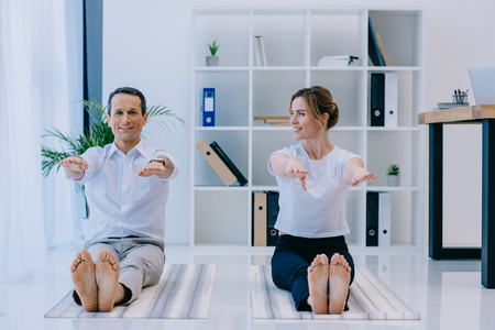 businessman with his trainer practicing yoga in Dandasana pose at office