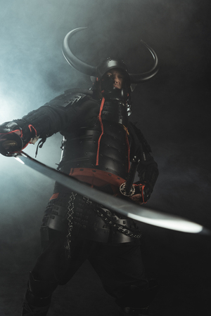 bottom view of samurai in traditional armor with sword on dark background with smoke