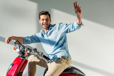 side view of young man waving to someone while sitting on red scooter