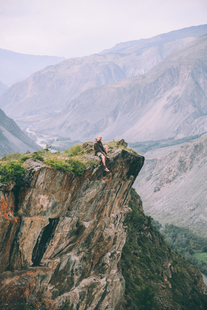 man sitting on cliff and looking at majestic mountains in Altai, Russia