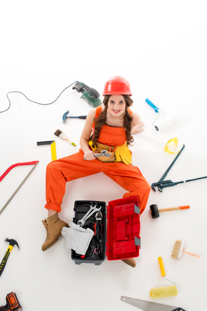 overhead view of girl in overalls sitting on floor with toolbox and different equipment, isolated on white