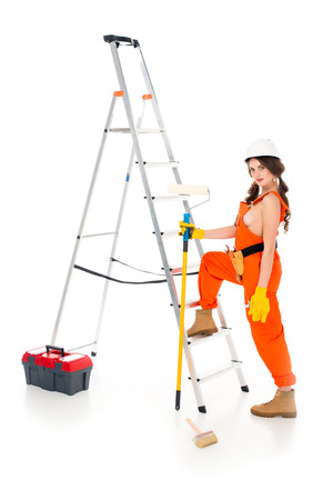 beautiful workwoman holding painting roller near ladder and toolbox, isolated on white