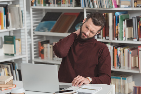tired student touching neck while working with laptop in library
