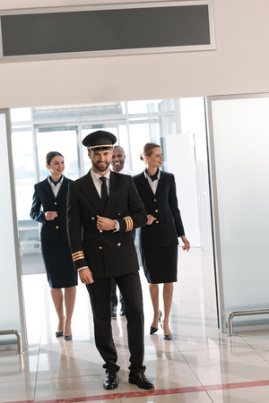 handsome young pilot walking by airport with his team Stockfoto