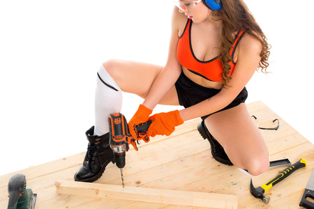 sexy girl in protective headphones working with electric drill at wooden table, isolated on white