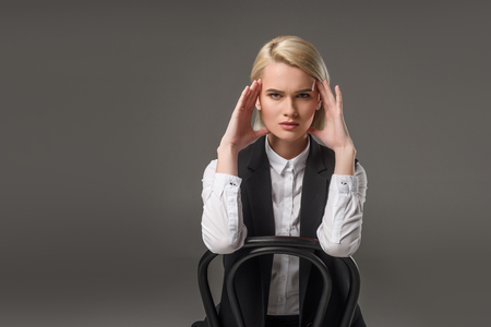 portrait of young stylish woman sitting on chair and looking at camera isolated on grey