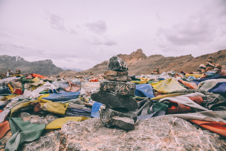 pile of stones and colorful prayer flags on mountain peak in Indian Himalayas, Ladakh region Stock Photo - 114328449