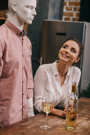 smiling woman looking at mannequin at table with wineglasses at home, perfect relationship dream concept