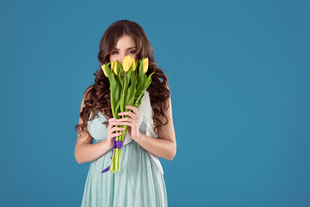 beautiful girl sniffing yellow tulips isolated on blue Imagens