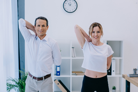 happy mature businessman stretching before workout with personal trainer