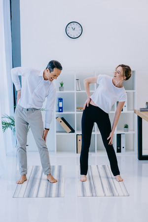 businesswoman with her trainer warming up before yoga practice at office