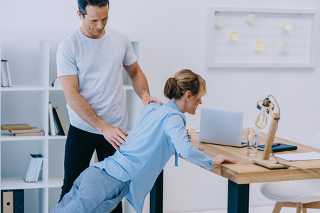 businesswoman doing oush ups on workdesk with trainer at office