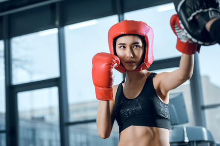 equiped young female boxer training at gym