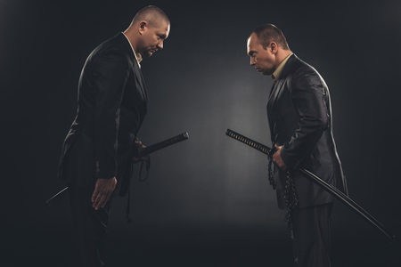 side view of modern samurai in suits bowing to each other isolated on black Stock Photo