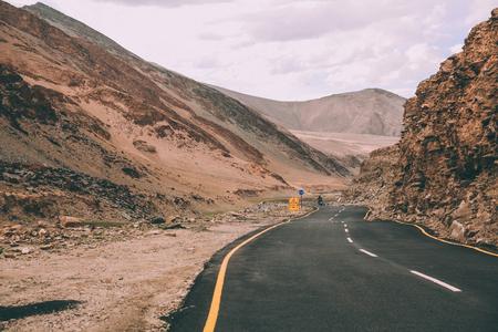 asphalt road with traffic signs in Indian Himalayas, Ladakh region