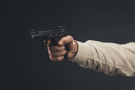 cropped shot of man holding gun isolated on black Stock Photo