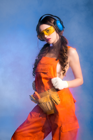 beautiful sexy girl in overalls with tool belt, goggles and protective headphones, isolated on blue