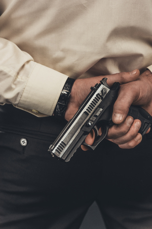 cropped shot of man in shirt holding gun behind back