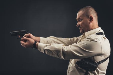 side view of man in shirt holding gun isolated on black Stock Photo