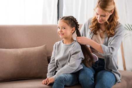 mother brushing hair to adorable smiling little daughter at home