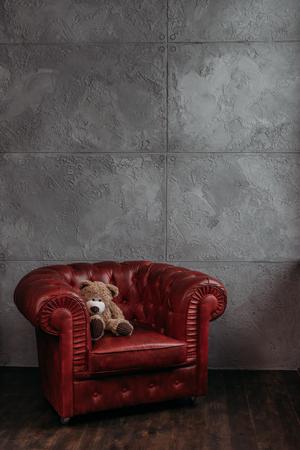 teddy bear on armchair at stylish room in loft style 免版税图像