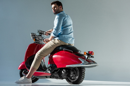 side view of fashionable young man riding red scooter