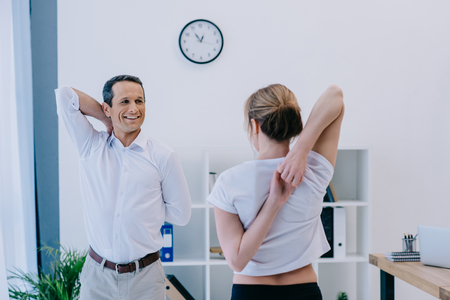 handsome mature businessman stretching before workout with personal trainer