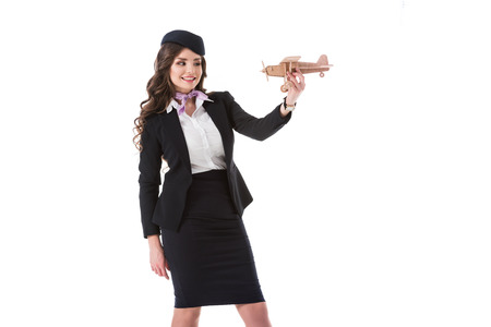 attractive stewardess holding wooden plane isolated on white