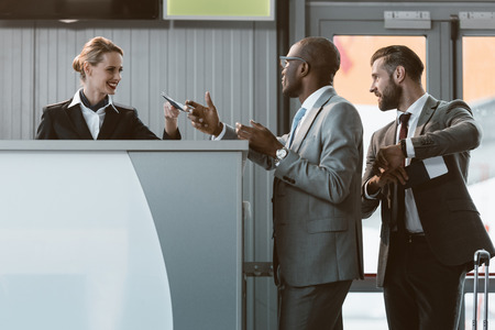 businessman standing at airport check in counter, hurry up on plane concept Stockfoto