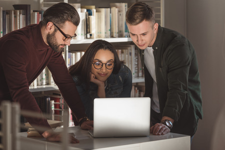 multicultural friends looking at laptop in library