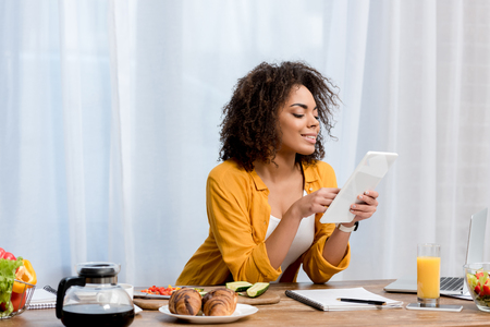 mixed race young woman using tablet at kitchen with food on table Banque d'images