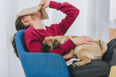 Pretty lady hugging pug and covering her face with book Banque d'images - 114330594