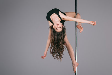 upside down of beautiful female dancer in sportswear exercising with pole and looking at camera on grey Stock Photo