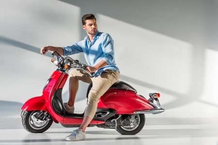 side view of young pensive man looking away while sitting on red scooter