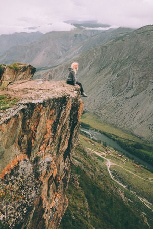 young woman sitting on cliff and looking at majestic mountains in Altai, Russia