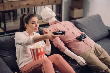 young woman eating popcorn while playing video game with manikin near by at home, loneliness concept Foto de archivo
