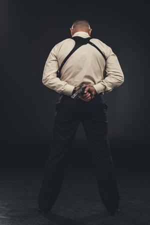 back view of killer in shirt holding gun behind back