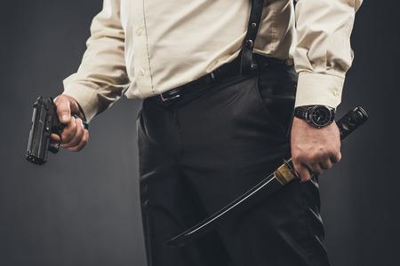 cropped shot of yakuza member with tanto knife and gun