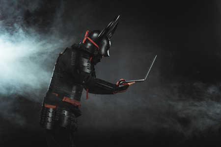 side view of of samurai using laptop on dark background with smoke