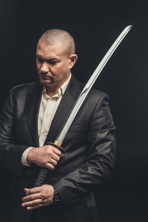 man in suit with katana sword isolated on black