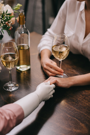 cropped shot of woman and mannequin holding hands at table with glasses of wine, unrequited love concept