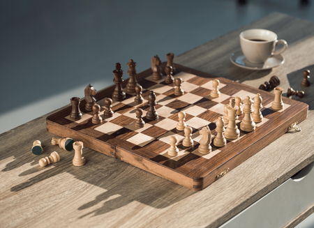 close-up view of chess board with pieces and cup of coffee on wooden table Stok Fotoğraf