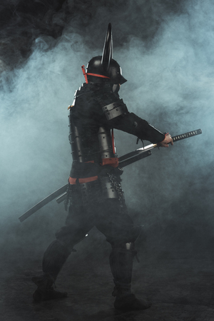 side view of samurai taking out his katana on dark background with smoke Banco de Imagens